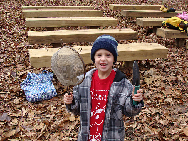 Photograph of a young student holding a net and a digging tool at a nature center